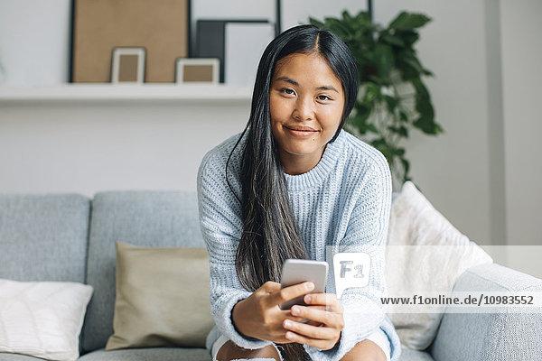Porträt einer lächelnden jungen Frau mit Smartphone auf der Couch zu Hause