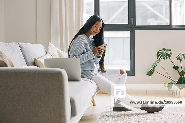 Young woman sitting on couch at home looking at smartphone