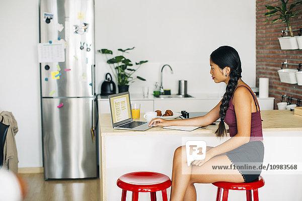 Frau bei der Arbeit mit dem Laptop am Küchenarbeitsplatz zu Hause