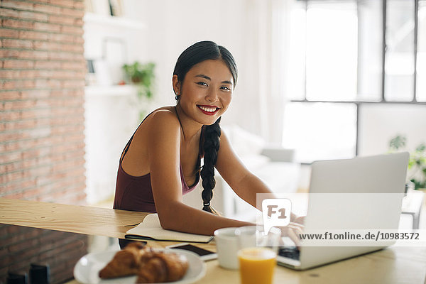 Porträt einer lächelnden Frau bei der Arbeit mit dem Laptop zu Hause