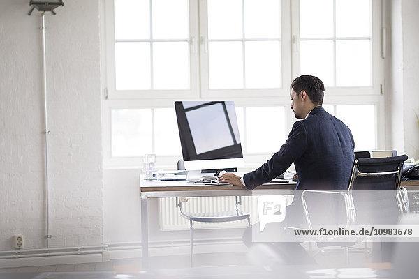 Geschäftsmann im Büro sitzend  am Computer arbeitend