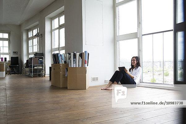 Geschäftsfrau  die barfuß auf dem Boden arbeitet