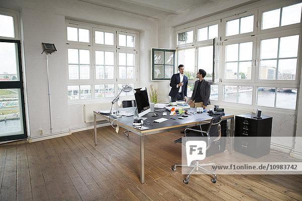 Zwei Geschäftsleute  die am Fenster stehen und reden.