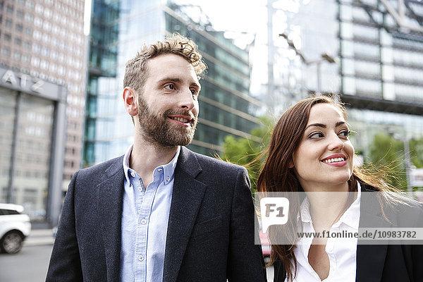 Lächelnder junger Geschäftsmann und Geschäftsfrau im Freien