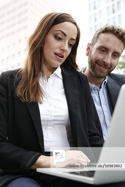Geschäftsmann und Geschäftsfrau mit Laptop im Freien