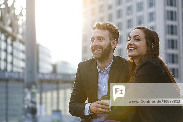 Lächelnde junge Geschäftsfrau und Geschäftsmann im Freien