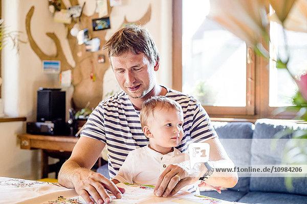 Vater und Sohn lesen Buch zu Hause