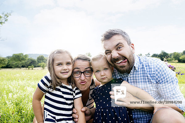 Portrait of family pulling funny faces