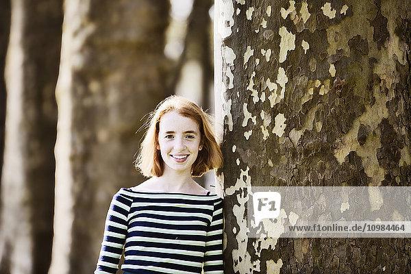Lächelndes Mädchen lehnt ageinst Baumstamm