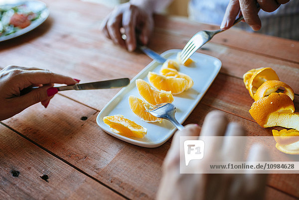 Hände von zwei Personen beim Essen von Orangenscheiben mit Besteck Hände von zwei Personen beim Essen von Orangenscheiben mit Besteck