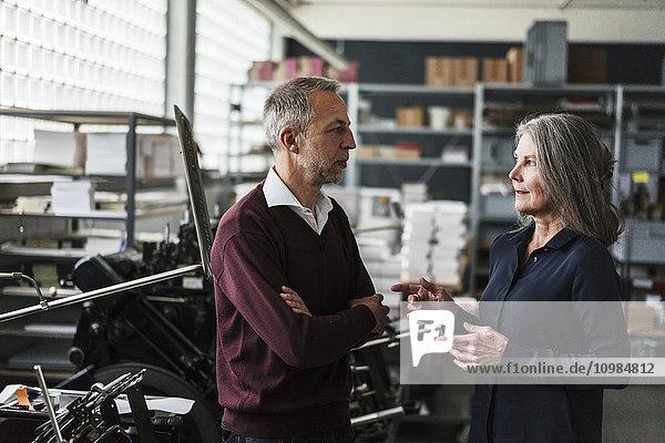 Seniorin und Seniorin im Gespräch in einer Druckerei