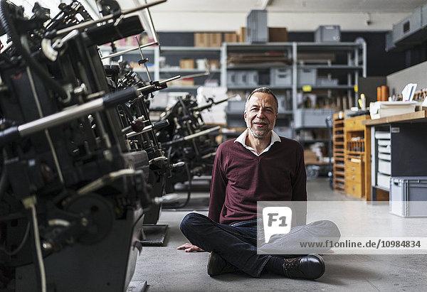 Lächelnder reifer Mann sitzt auf dem Boden einer Druckerei