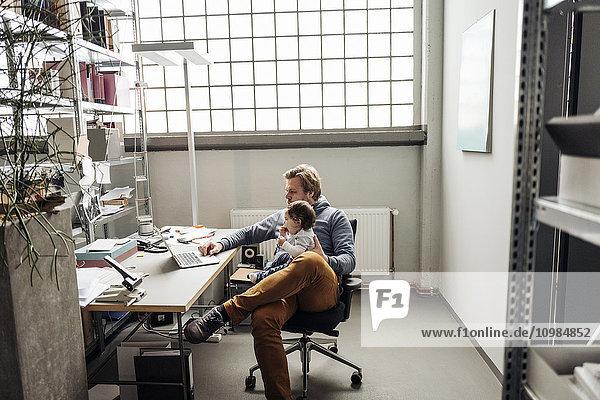 Mann mit Baby auf dem Schoß mit Laptop am Schreibtisch in einer Fabrik