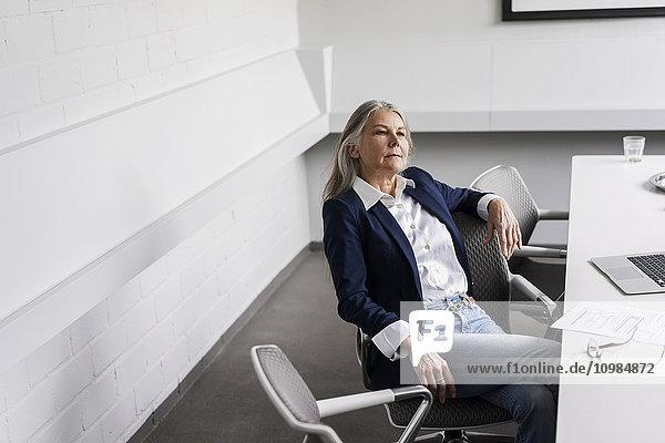 Senior Geschäftsfrau am Konferenztisch sitzend