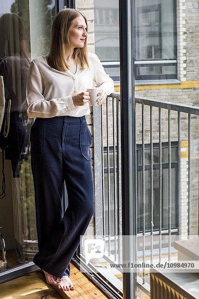 Frau mit Kaffeetasse steht vor offener Glastür und schaut in die Ferne. Frau mit Kaffeetasse steht vor offener Glastür und schaut in die Ferne.