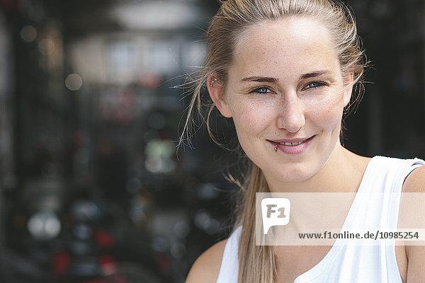 Porträt einer lächelnden jungen Frau mit Lippenpiercing