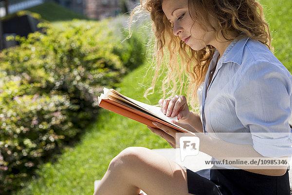 Frau sitzt auf einer Treppe und liest ein Buch.
