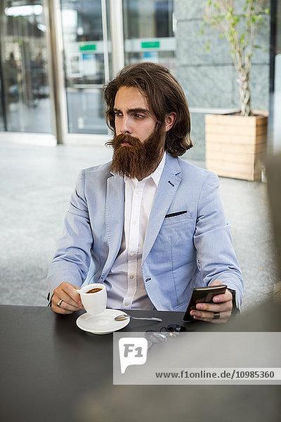 Stilvoller Geschäftsmann mit Handy im Café
