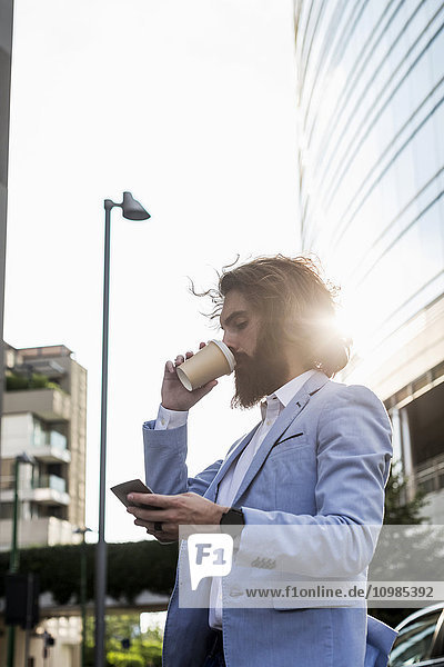 Stilvoller Geschäftsmann mit Handy und Kaffee für unterwegs