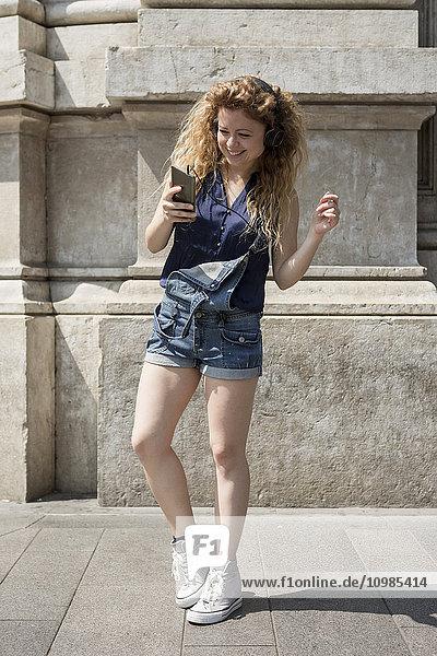Lächelnde junge Frau mit Kopfhörer und Smartphone