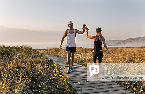 Spain  Aviles  athletes couple hitting five on the beach in the evening