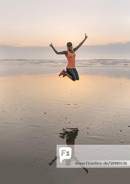 Junge Sportlerin beim abendlichen Springen am Strand