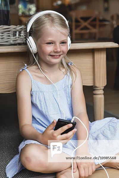 Porträt eines glücklichen kleinen Mädchens beim Musikhören mit Kopfhörer und Smartphone