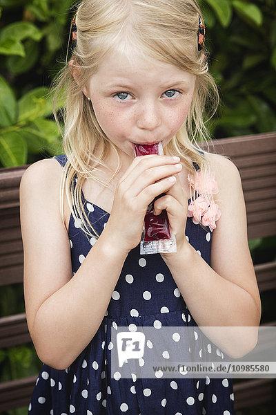Blondes kleines Mädchen beim Essen von Wassereis