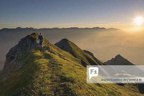 Österreich  Tirol  Wanderer am Grat bei Sonnenaufgang