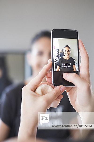 Hände der Visagistin beim Fotografieren mit dem Smartphone ihrer glücklichen Kundin