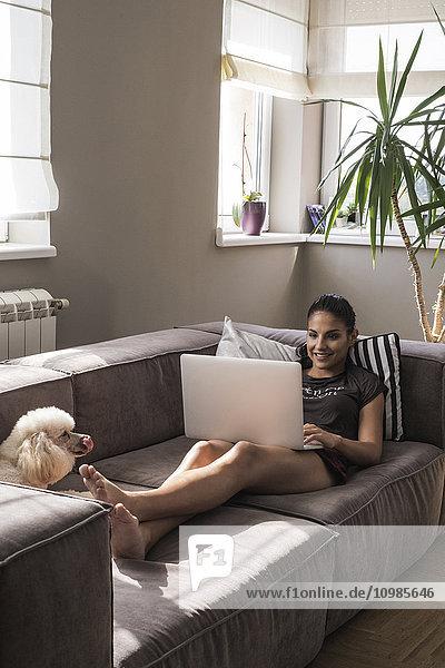 Junge Frau sitzt mit ihrem Hund auf der Couch und benutzt einen Laptop.