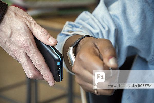 Frau bezahlt mit smartwatch und NFC-Leser