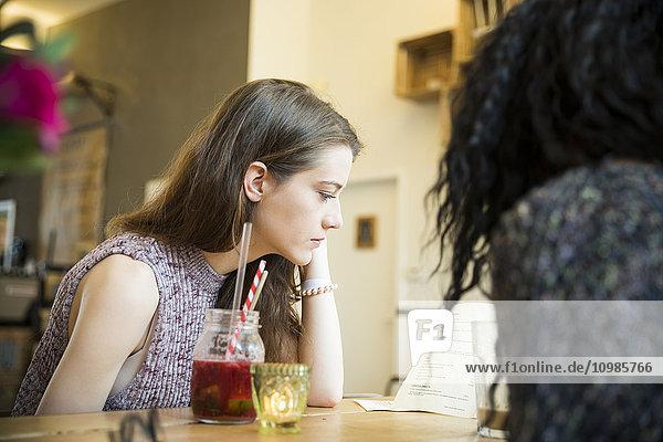 Zwei Freunde im Café bei der Speisekarte