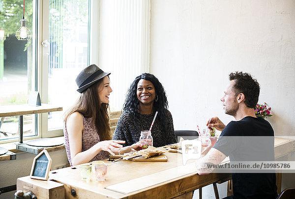 Freunde treffen sich im Café  essen und Spaß haben