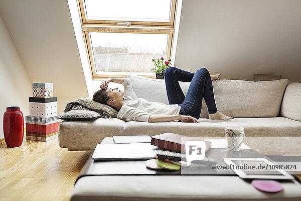 Entspannte Frau auf der Couch liegend