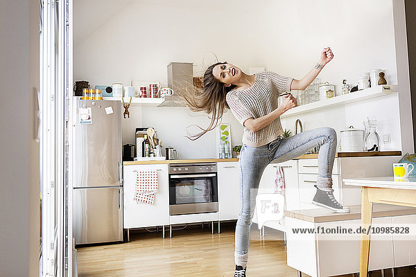 Playful young woman in kitchen