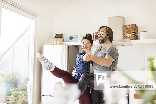 Smiling couple dancing in kitchen