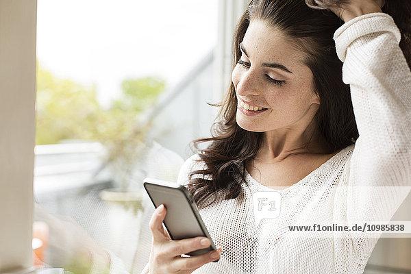 Lächelnde junge Frau beim Anblick des Handys