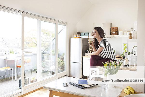 Lächelnde junge Frau entspannt in der Küche