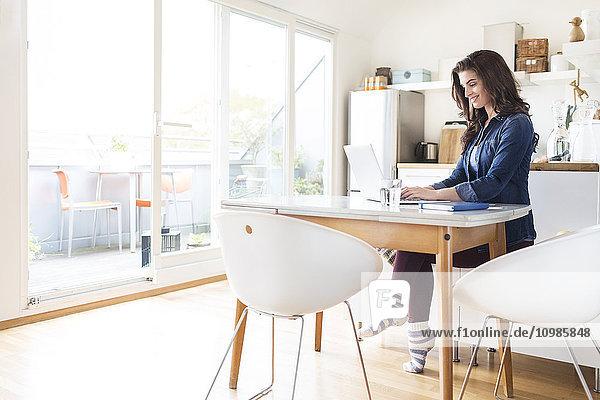 Lächelnde junge Frau zu Hause mit Laptop