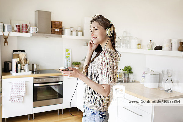 Lächelnde junge Frau in der Küche beim Musikhören