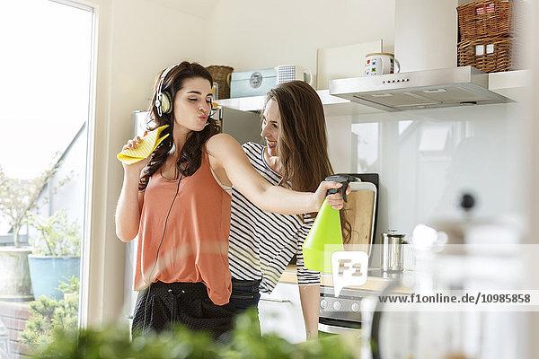 Zwei glückliche Frauen in der Küche putzen und Musik hören