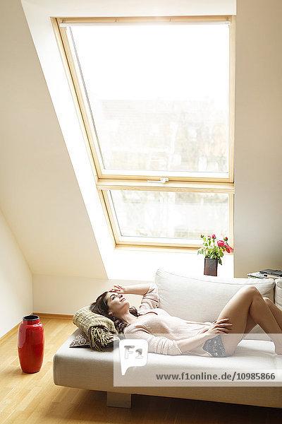 Entspannte Frau  die auf der Couch liegt und aus dem Fenster schaut.