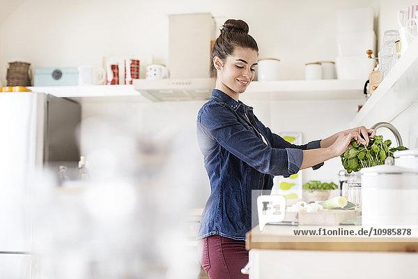 Junge Frau in der Küche bei der Zubereitung von Speisen