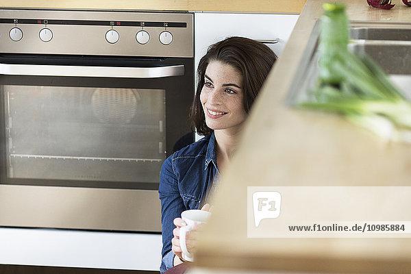 Junge Frau mit einer Tasse Kaffee zum Entspannen in der Küche