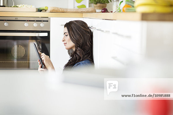 Junge Frau mit digitalem Tablett in der Küche