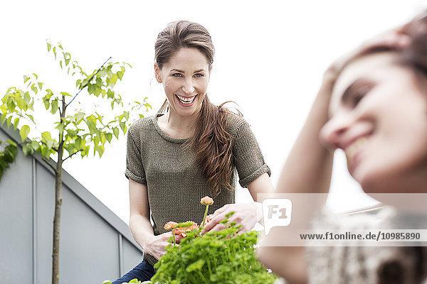 Glückliche junge Frau mit Freundin auf dem Balkon