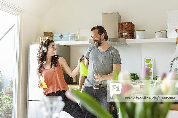 Glückliche Frau mit Mann in der Küche beim Putzen und Musik hören