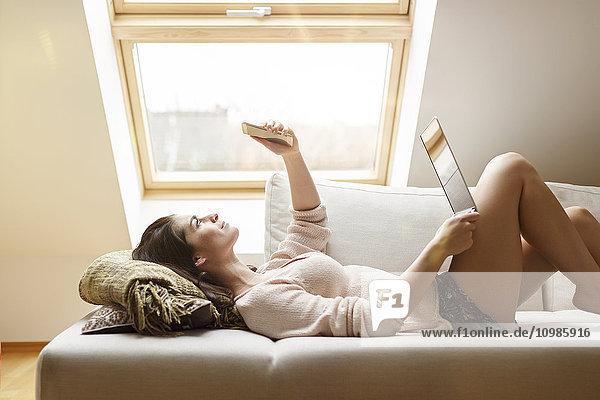 Entspannte Frau auf der Couch liegend mit Handy und Laptop