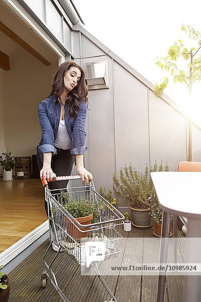 Junge Frau mit Topfpflanze im Einkaufswagen auf dem Balkon